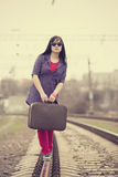 Young fashion girl with suitcase at railways. Royalty Free Stock Image
