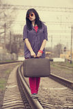 Young fashion girl with suitcase at railways. Stock Image