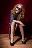 Young fashion girl with sunglasses sitting on a chair and shouts Royalty Free Stock Photos