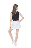 Young fashion girl in white skirt posing isolated. Back Stock Photo