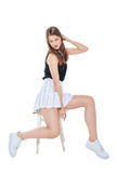 Young fashion girl in white skirt sitting on the chair isolated royalty free stock image