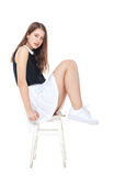 Young fashion girl in white skirt sitting on the chair isolated Stock Image