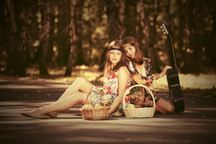 Young fashion girls with fruit baskets in summer forest. Two young fashion girls with fruit baskets in summer forest Stock Photography