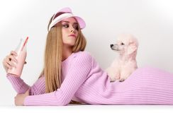Young fashion glamour woman in winter long dress and cap holding pink poodle dog and drinking from bottle. Young fashion glamour woman lying in winter long dress Stock Images