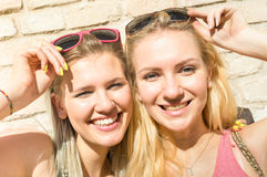 Young fashion happy women girls taking summer selfie. Young fashion women girls taking selfie against stonewall - Summer concept with happy girlfriends having Stock Photo