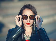 Young fashion hipster beautiful girl in leather jacket and sungl Royalty Free Stock Photography