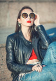 Young fashion hipster beautiful girl in leather jacket and sungl Stock Photos