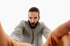 Young fashion hipster crazy blogger recording video blog or selfie for his followers. Young funny bearded hipster blogger man in modern casual style holding stock photo