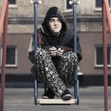 Young fashion hipster man sitting on the swing. Young fashion hipster man in a hoodie sitting on the swing Royalty Free Stock Images