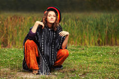 Young fashion hipster woman in rasta poncho sitting on the ground. Happy young fashion hipster woman in rasta poncho sitting on the ground outdoor Royalty Free Stock Photo