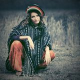 Young fashion hipster woman in rasta poncho sitting on the ground Stock Photos