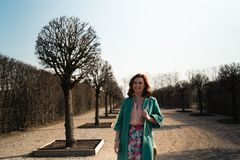 Young fashion lover woman waling in a park wearing vivid green jacket and a colorful skirt stock photos