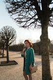 Young fashion lover woman waling in a park wearing vivid green jacket and a colorful skirt royalty free stock photography