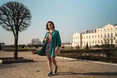 Young fashion lover woman waling in a park wearing vivid green jacket and a colorful skirt royalty free stock photos