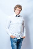 Young fashion male model wearing bow tie on gray Stock Images