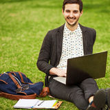 Young fashion male student sitting on grass Royalty Free Stock Images