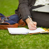 Young fashion male student sitting on grass Stock Image