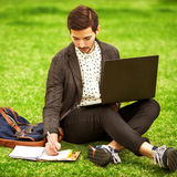 Young fashion male student sitting on grass Stock Photos