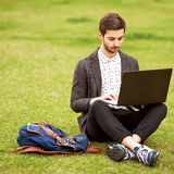 Young fashion male student sitting on grass Royalty Free Stock Image