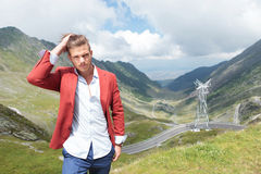 Young fashion man adjusts hair outdoors Stock Photo