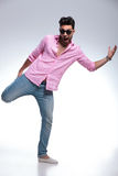 Young fashion man balancing with one leg in his hand Royalty Free Stock Photos