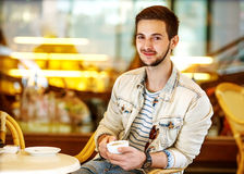 Young fashion man with beard drinking espresso coffee in the cit Stock Photography