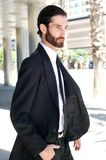 Young fashion man with beard walking outside in the city Stock Photography