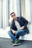 Young, fashion man in black leather jacket, sunglasses and jeans. Outdoor portrait Stock Images