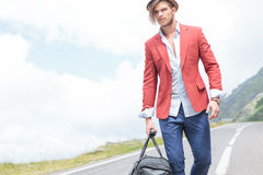 Young fashion man carries bag outdoor Royalty Free Stock Photo