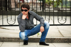 Young fashion man at the cast iron fence Stock Photo