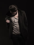 Young fashion man checking his coat for the price tag. On dark studio background Stock Photography