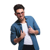 Young fashion man fixing his jeans shirt Royalty Free Stock Images