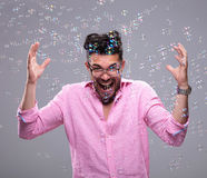 Young fashion man goes crazy among bubbles Stock Images