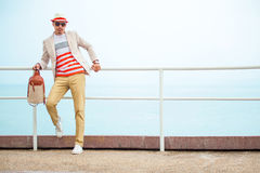 Young fashion man in hat holding bag near sea. Young cute fashion man in hat and glasses holding bag near sea royalty free stock photo