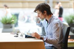 Young fashion man / hipster drinking espresso coffee in the city cafe Royalty Free Stock Photo