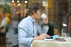 Young fashion man / hipster drinking espresso coffee in the city cafe Royalty Free Stock Images