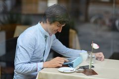 Young fashion man / hipster drinking espresso coffee in the city cafe Stock Photo
