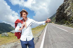 Young fashion man hitchhikes Stock Image