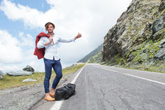 Young fashion man hitchhikes with joy Stock Image