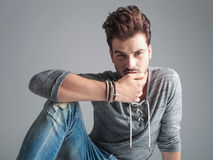 Young fashion man holding his thumb on his lips Royalty Free Stock Images