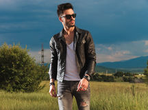 Young Fashion Man In Leather Jacket And Sunglasses Walking