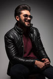 Young fashion man with long beard laughing while looking away. Side view of a dramatic young fashion man with long beard laughing while looking away from the Royalty Free Stock Photography