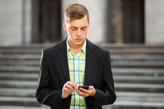 Young fashion man with a mobile phone outdoor Royalty Free Stock Images