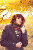 Young fashion man portrait dressed in gray jacket and striped sweater, oudoor in autumn park. Stock Images