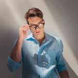 Young fashion man putting on his glasses. Royalty Free Stock Photos