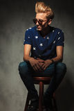 Young fashion man is resting on a stool Royalty Free Stock Images