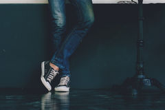Young fashion man`s legs in blue jeans and black sneakers on wooden floor. Stock Image