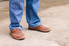 Young fashion man`s legs in blue jeans and brown boots on concre Stock Photography