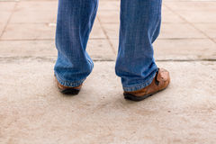 Young fashion man`s legs in blue jeans and brown boots on concre Stock Image