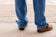 Young fashion man`s legs in blue jeans and brown boots on concre Royalty Free Stock Photos
